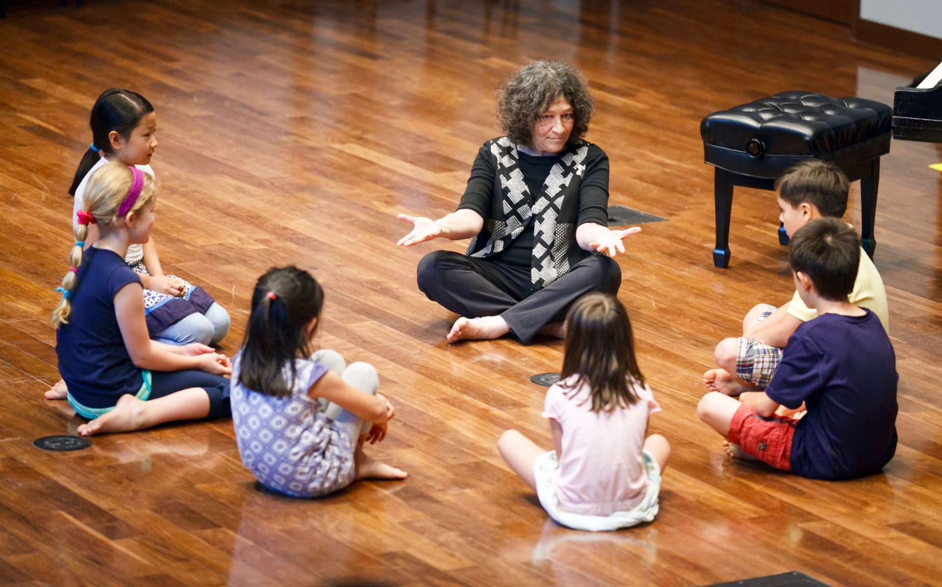 Young students in a Dalcroze class watch their teacher closely.